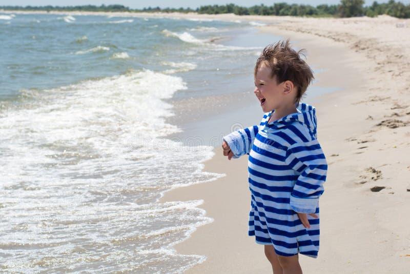 Das Kind steht durch das Meer auf dem Hintergrund des Strandes in einer gestreiften Robe und der Blicke in den Abstand glücklich stockfotografie