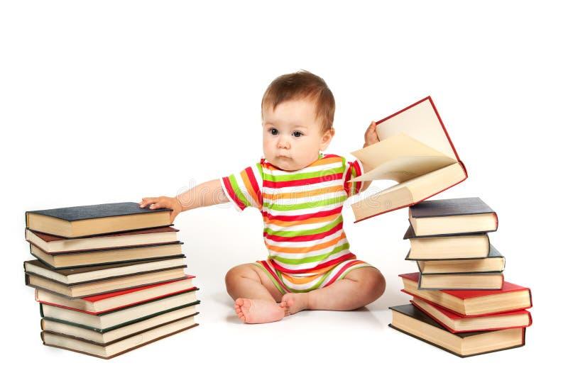 Das Kind und ein Stapel der Bücher lizenzfreie stockfotos