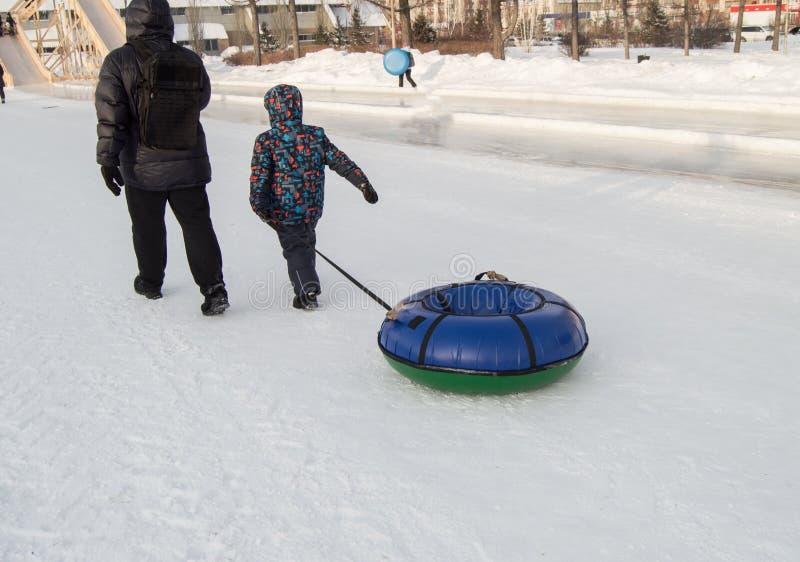 Das Kind und sein Vater schleppen einen Schlittenschläuche für das Ski fahren hinunter den Hügel im Stadt Park im Winter stockbild