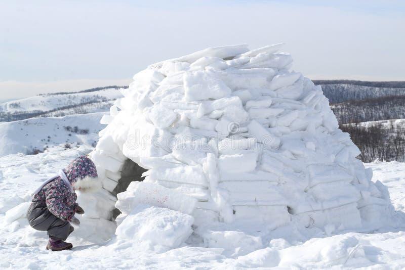 Das Kind untersucht das Haus des Eskimo-Iglus lizenzfreie stockfotografie