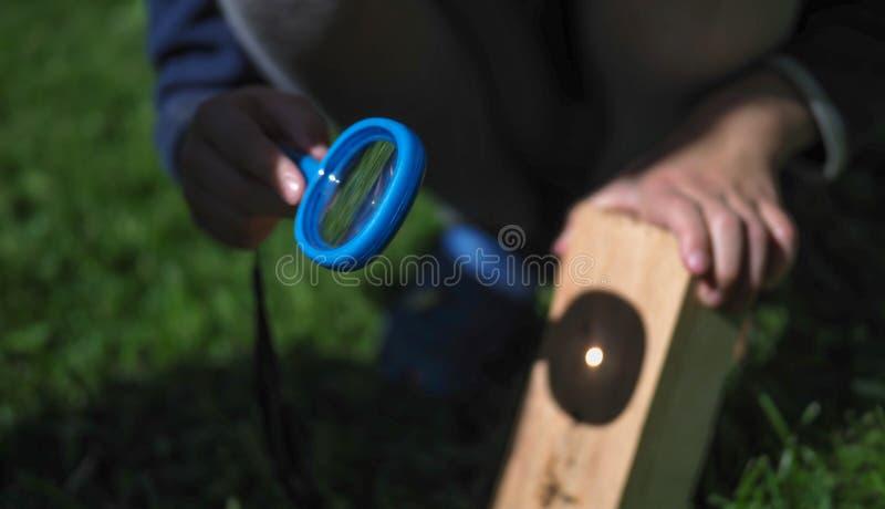 Das Kind verbrennt eine Lupe stockfotos