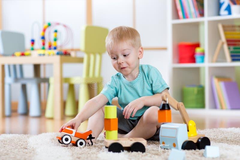 Das Kinderjungenkleinkind, das Auto spielt, spielt zu Hause lizenzfreie stockfotografie