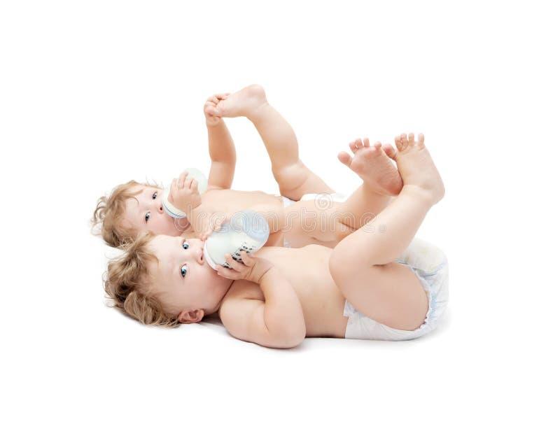 Das Kinderzwillingslügen saugen Milchflaschen stockfotografie