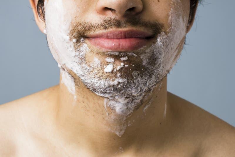 Das Kinn des jungen Mannes bedeckt, wenn Schaum rasiert wird stockfotografie