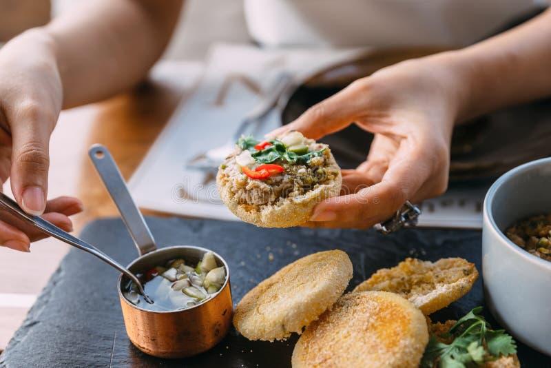 Das Kleben des gegrillten Schweinefleisch überstieg mit Koriander auf einem Belag des englischen Muffins mit in Essig eingelegtem lizenzfreies stockbild