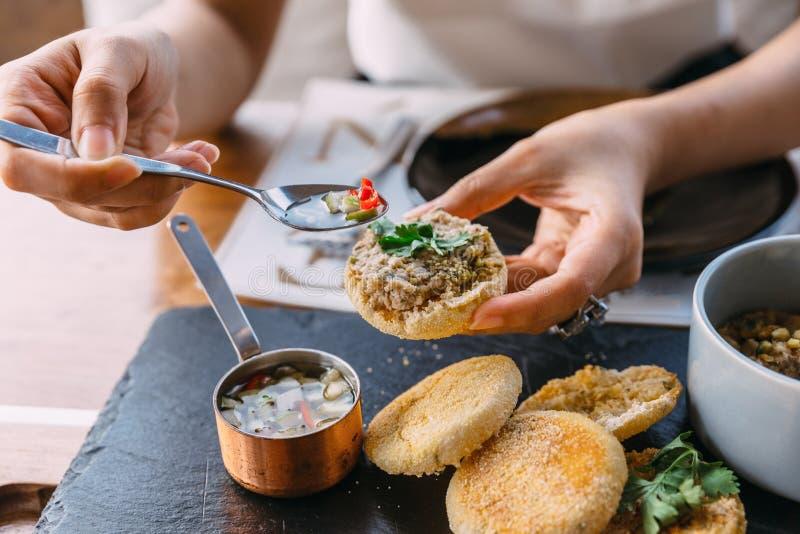 Das Kleben des gegrillten Schweinefleisch überstieg mit Koriander auf einem Belag des englischen Muffins mit in Essig eingelegtem stockbild
