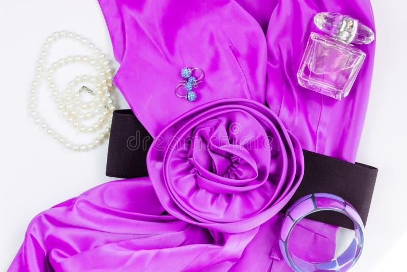 Das Kleid und die Zusätze der hellen Rosafrauen auf einem weißen Hintergrund Blumengurt, Perlenhalskette, Ohrringe, Armband und P lizenzfreies stockfoto