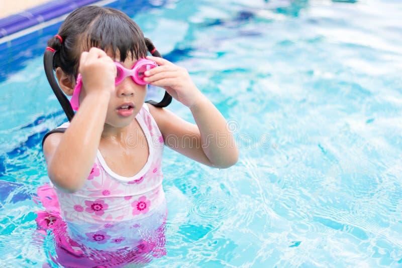 Das kleine asiatische Mädchen, das wasserdichte sunglassses trägt, versuchen, Al zu schwimmen lizenzfreie stockfotos