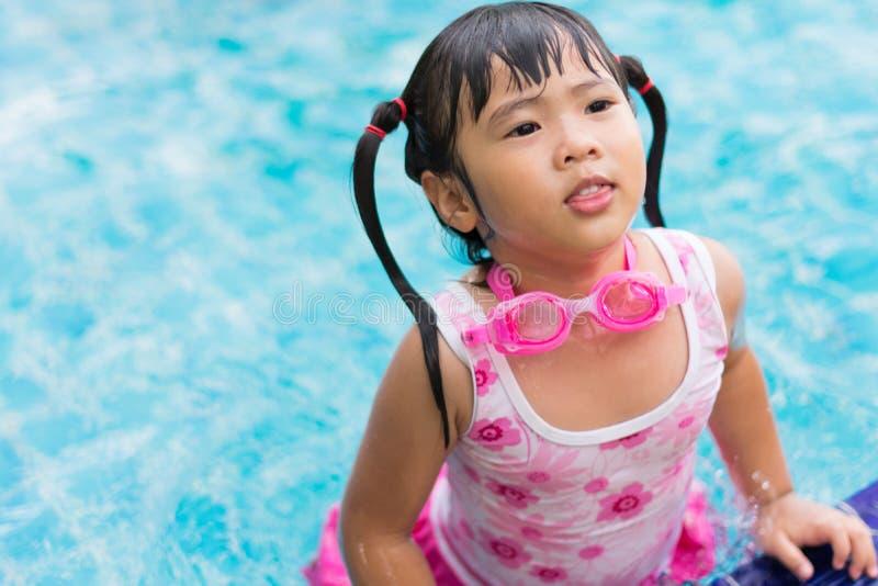 Das kleine asiatische Mädchen, das wasserdichte sunglassses trägt, versuchen, Al zu schwimmen lizenzfreies stockbild