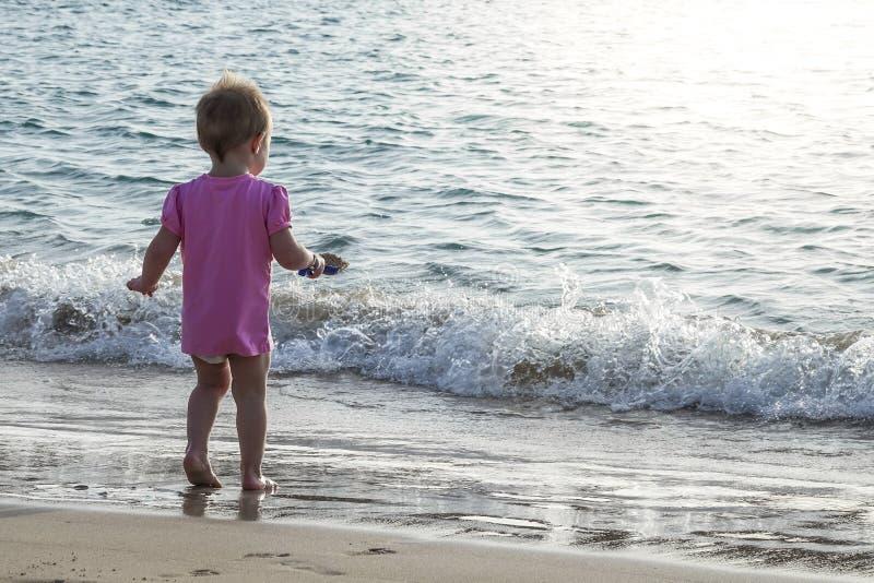 Das kleine Baby, das im Wasser spielt, umranden auf dem Strand lizenzfreie stockfotos