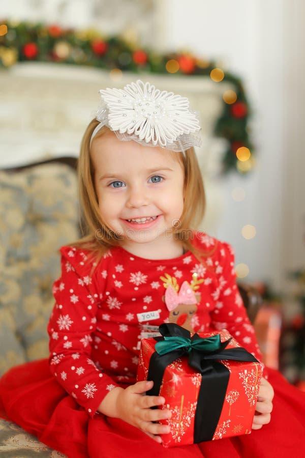 Das kleine glückliche Mädchen, das rotes Kleid trägt, Geschenk hält und auf Sofa nahe sitzt, verzierte Kamin lizenzfreie stockbilder