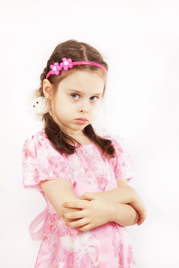 Das kleine hübsche Mädchen, das schönes rosa Kleid trägt, ist verärgert stockbild