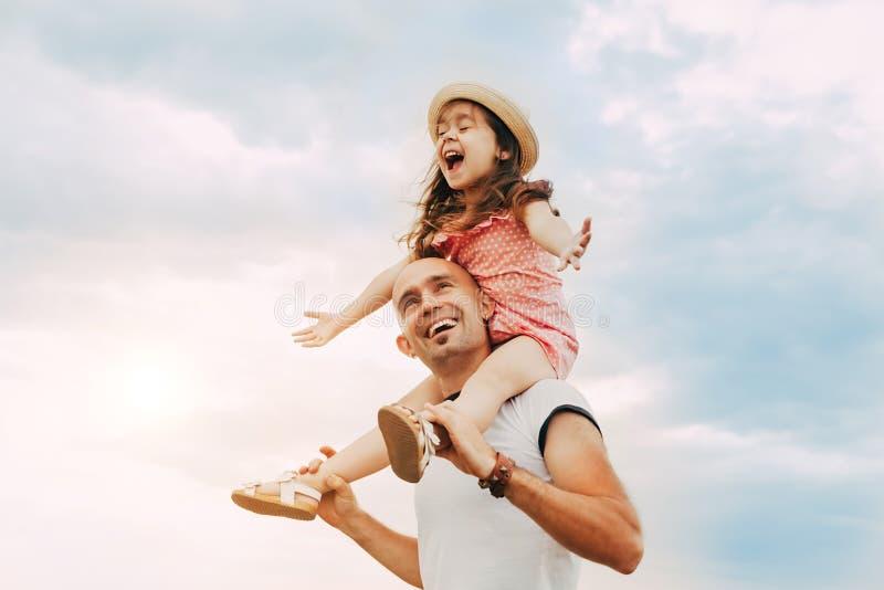 Das kleine Mädchen, das auf Vater ` s sitzt, schultert lizenzfreies stockbild