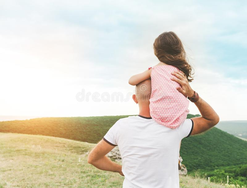 Das kleine Mädchen, das auf Vater ` s sitzt, schultert stockbilder