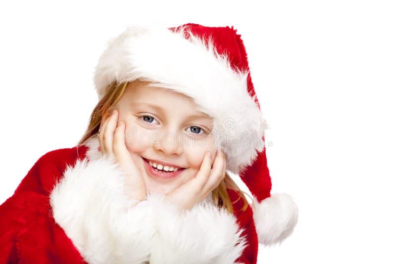 Das kleine Mädchen, das als Weihnachtsmann gekleidet wird, lächelt glücklich stockfotos