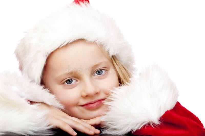 Das kleine Mädchen, das als Weihnachtsmann gekleidet wird, lächelt glücklich stockbilder