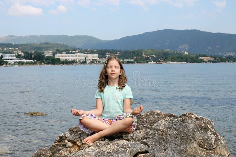 Das kleine Mädchen, das auf einem Felsen sitzt und meditiert stockfotografie