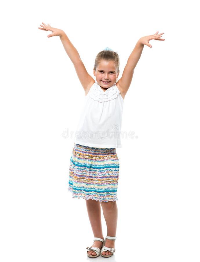 das kleine Mädchen, das auf weißem Hintergrund steht, hob ihre Hände oben an stockfotografie