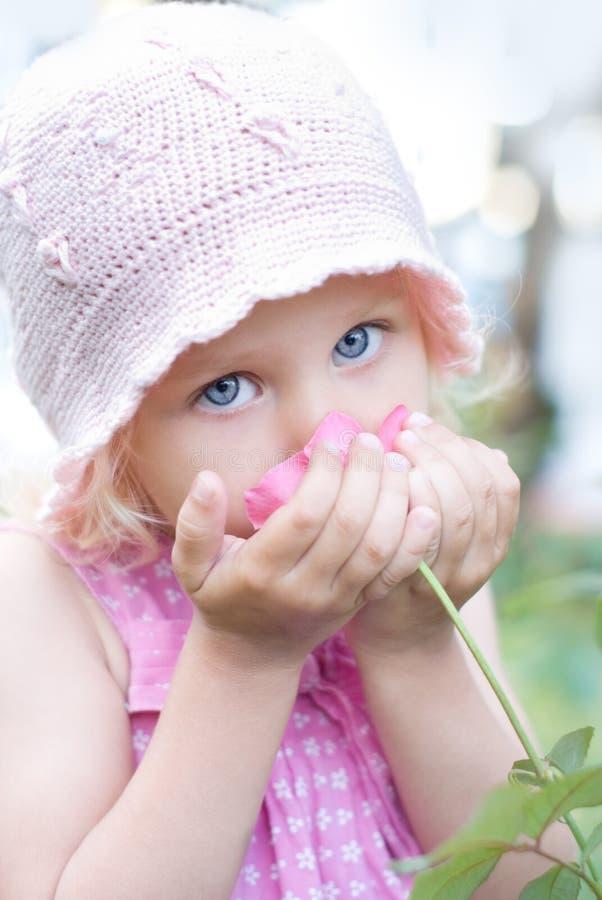 Das kleine Mädchen, das ein rosafarbenes riecht, stieg stockfotografie