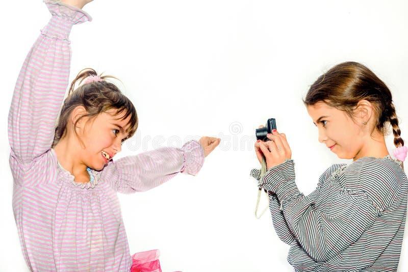 Das kleine Mädchen, das Fotos ihrer Schwester mit Kamera macht, lokalisierte O stockbild
