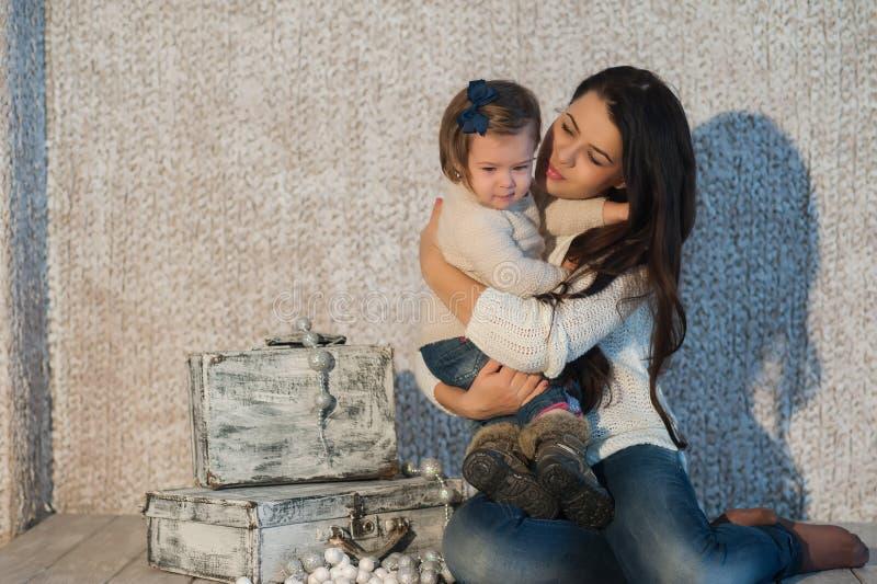 Das kleine Mädchen, das mit ihrer Mutter in einem netten Winter streichelt, kleidet, Baby, Lebensstil, Kindheit, Freude, Familien lizenzfreies stockfoto