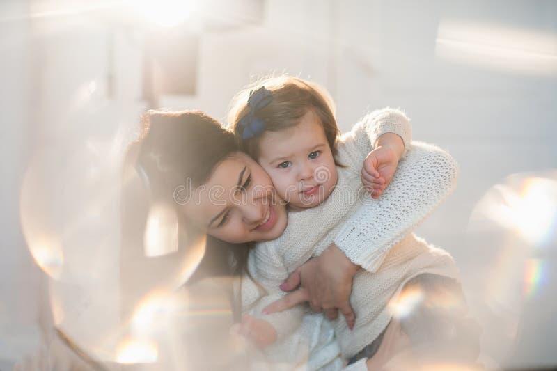 Das kleine Mädchen, das mit ihrer Mutter in einem netten Winter streichelt, kleidet, Baby, Lebensstil, Kindheit, Freude, Familien lizenzfreies stockbild