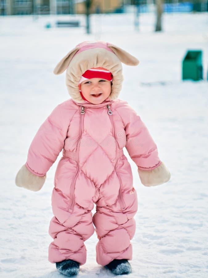 Das kleine Mädchen ein Jähriges unternimmt die ersten Schritte auf dem Winterpark lizenzfreie stockbilder