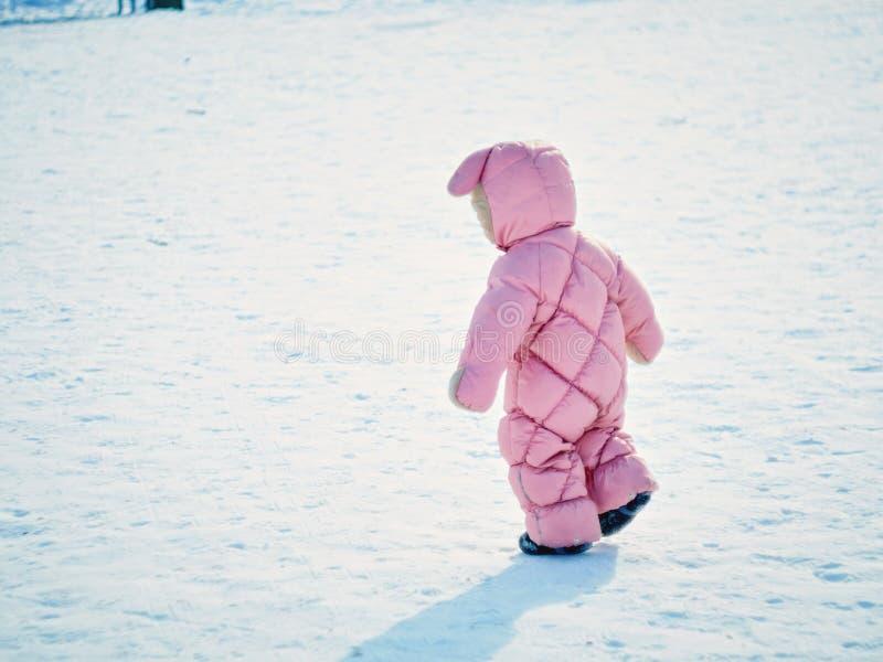 Das kleine Mädchen ein Jähriges unternimmt die ersten Schritte auf dem Winterpark lizenzfreies stockbild