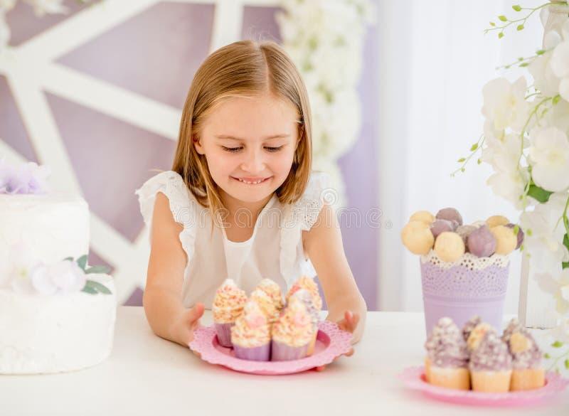Das kleine Mädchen, das eine rosa Platte mit Bonbon hält, backt im Schokoriegel zusammen lizenzfreie stockfotografie