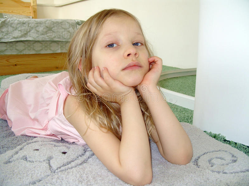 Das kleine Mädchen in einem rosafarbenen Kleid, starrend uns an. lizenzfreies stockfoto
