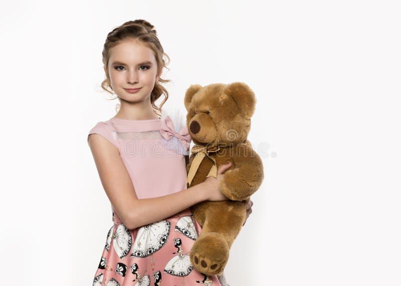 Das kleine Mädchen, das einen Teddybären hält, betreffen einen weißen Hintergrund Freier Platz für Text lizenzfreie stockbilder