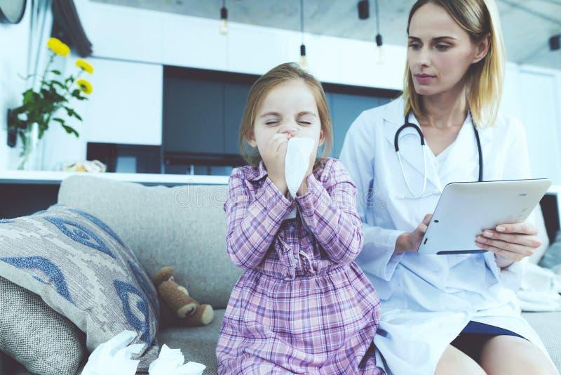 Das kleine Mädchen fiel krank Ein Doktor kam, sie zu sehen Das Mädchen brennt ihre Nase in einer Serviette durch Der Doktor füllt lizenzfreies stockbild