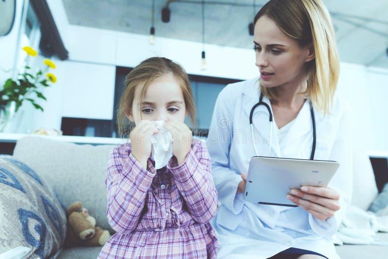 Das kleine Mädchen fiel krank Ein Doktor kam, sie zu sehen Das Mädchen brennt ihre Nase in einer Serviette durch Der Doktor füllt lizenzfreie stockfotografie