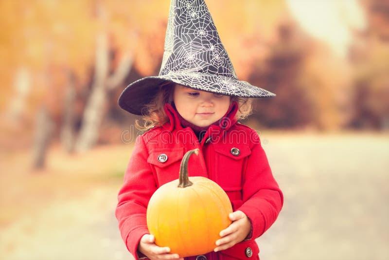 Das kleine Mädchen, das Halloween-Hexenhut trägt und wärmen roten Mantel und haben Spaß im Herbsttag stockbild