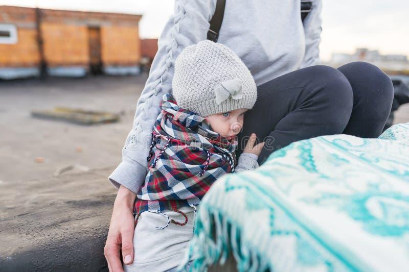 Das kleine Mädchen hat sich auf der Mutter angeschmiegt Schlechtes Wetter, Kälte, Wind lizenzfreie stockfotos