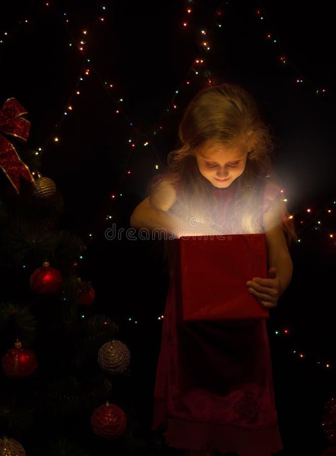 Das kleine Mädchen im Standort des neuen Jahres schaut in einer Geschenkbox lizenzfreie stockbilder