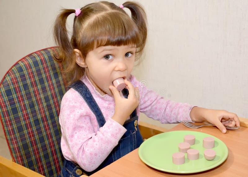Das kleine Mädchen isst Wurst mit den Händen stockfotografie