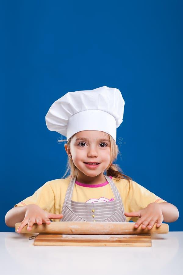 Das kleine Mädchen ist, zubereitend kochend und Lebensmittel auf blauem Hintergrund stockbild