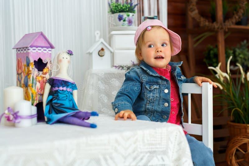 Das kleine Mädchen mit den Puppenhasen geht und lächelt lizenzfreie stockfotografie