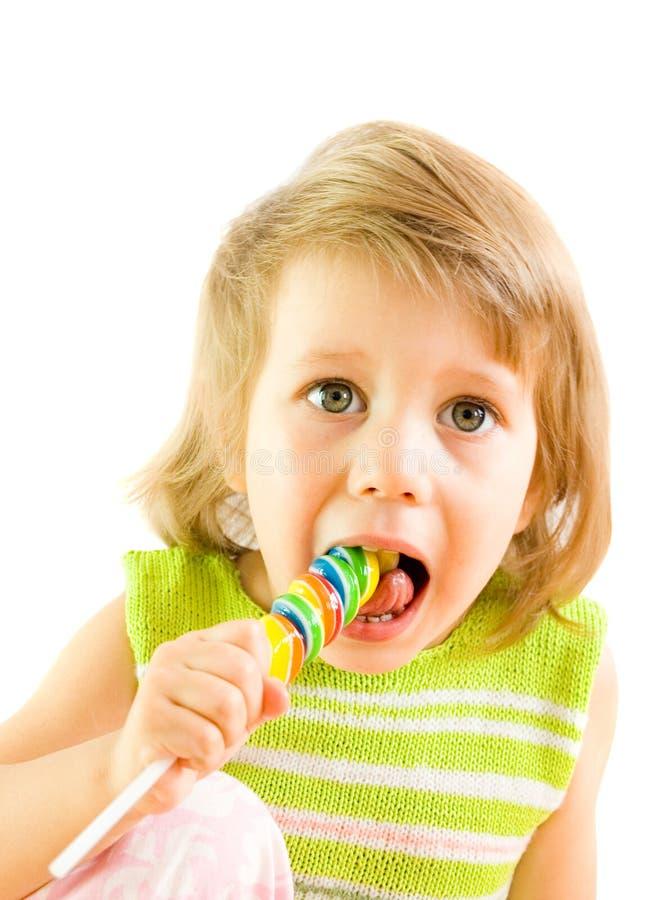 Das kleine Mädchen mit einem Bonbon lizenzfreies stockfoto