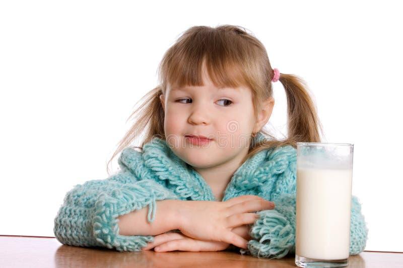 Das kleine Mädchen mit einem Milchglas lizenzfreie stockfotografie