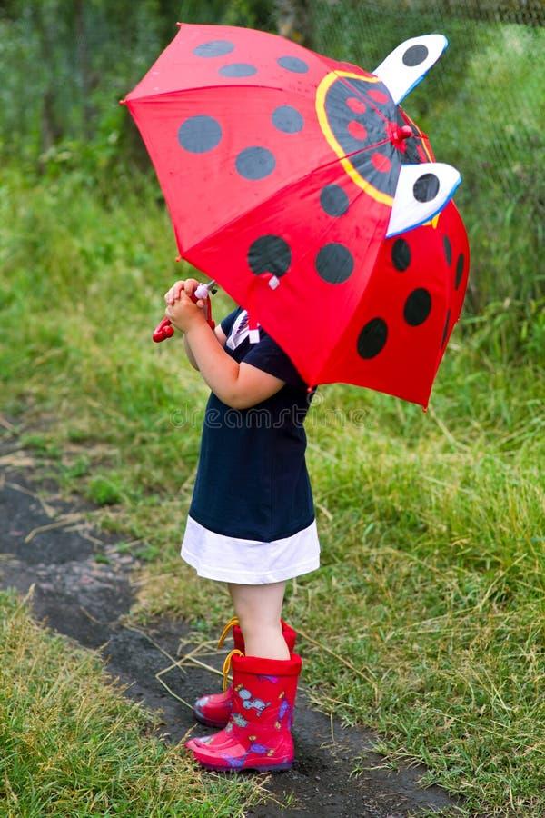 Das kleine Mädchen mit einem Regenschirm stockbild