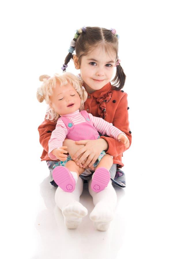 Das kleine Mädchen mit einer Puppe getrennt auf einem Weiß lizenzfreie stockfotografie