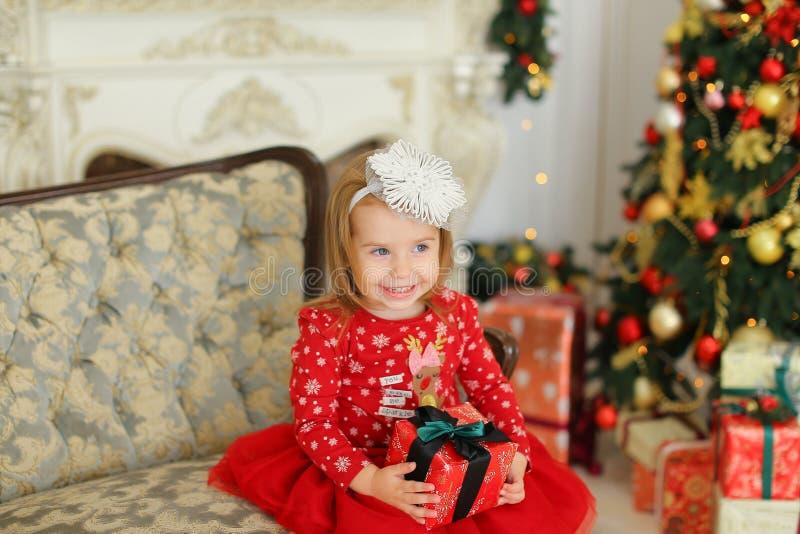 Das kleine Mädchen, das rotes Kleid trägt, Geschenk hält und auf Sofa nahe sitzt, verzierte Kamin lizenzfreie stockfotos