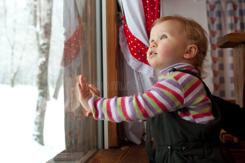 Das kleine Mädchen schaut heraus das Fenster stockbilder