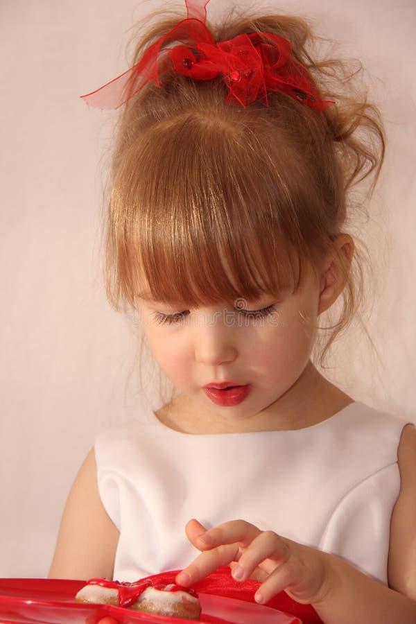Das kleine Mädchen schmeckt den kleinen Kuchen stockfoto