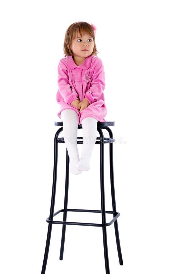 Das kleine Mädchen sitzt auf einem hohen Stuhl lizenzfreie stockfotos