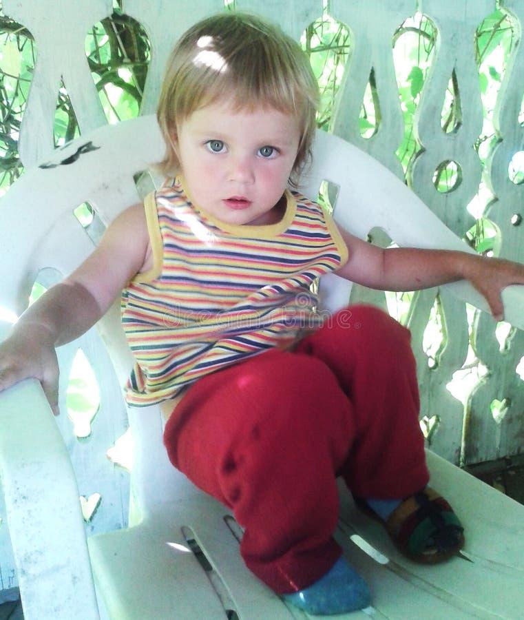 Das kleine Mädchen sitzt auf einem Stuhl stockfotografie