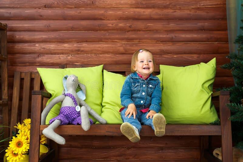 Das kleine Mädchen sitzt und lächelt stockfotos