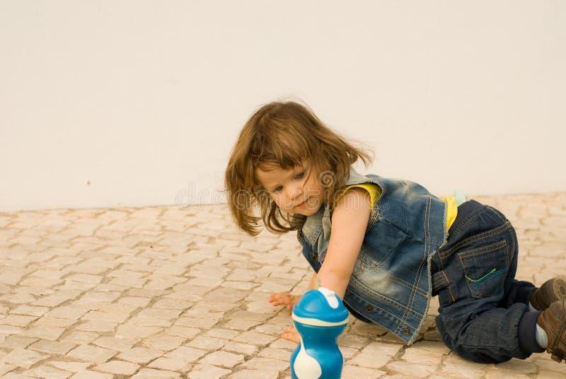 Das kleine Mädchen spielt auf dem Kopfstein stockbilder